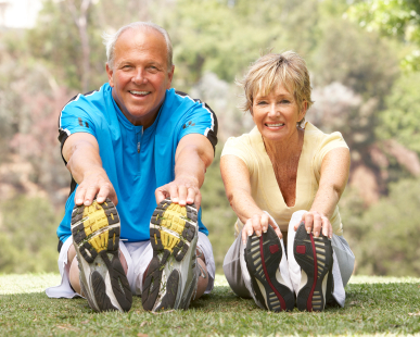 Senior Couple Exercising In Park - Enjoy Retirement